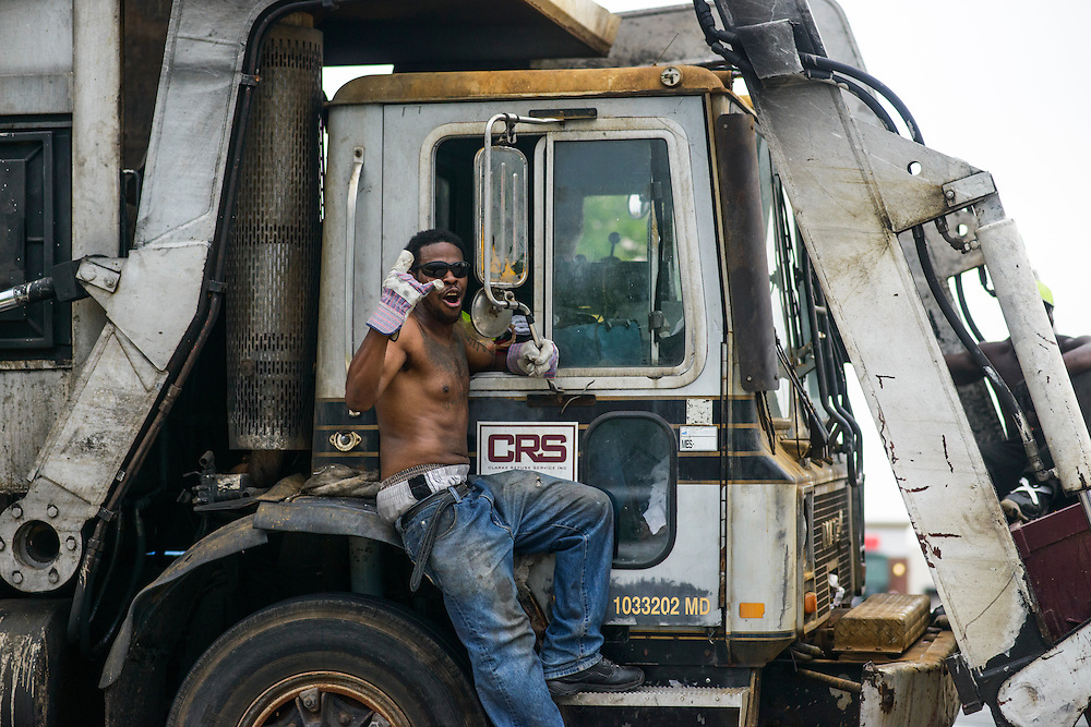 Baltimore County, Maryland - May 27, 2014: Guys riding inside a dumpster in front of a trash truck and on the side of the garbage truck.<br /> Photo by Matt Roth