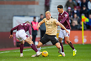 Curtis Main (#9) of Aberdeen FC shields the ball from Euan Henderson (#41) and Sean Clare (#8) of Heart of Midlothian FC during the Ladbrokes Scottish Premiership match between Heart of Midlothian FC and Aberdeen FC at Tynecastle Stadium, Edinburgh, Scotland on 29 December 2019.