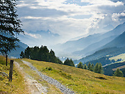 """Forested ridges of Upper Engadine descend to Zuoz village in Graubünden canton, Grison Alps, Switzerland, Europe. The Swiss valley of Engadine translates as the """"garden of the En (or Inn) River"""" (Engadin in German, Engiadina in Romansh, Engadina in Italian)."""