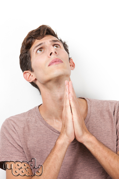 Sad young man with hands clasped praying over white background