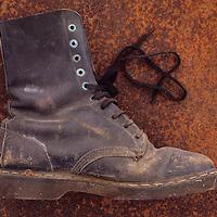 Well-worn black heavy-duty industrial working boot lying on rusty metal sheet