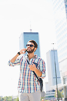 Happy man looking away while using cell phone in city