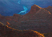 The early morning sun kisses the slopes of Escalante and Cardenas buttes as the Colorado River flows through the blue shadows of the canyon. From the South Rim of Grand Canyon National Park.