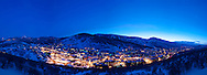 Park City, Utah at dusk with Park City Mountain Resort and Deer Valley Resort in background.