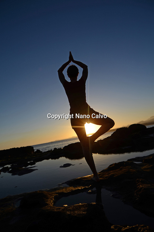 Young woman in tree pose, on the coast