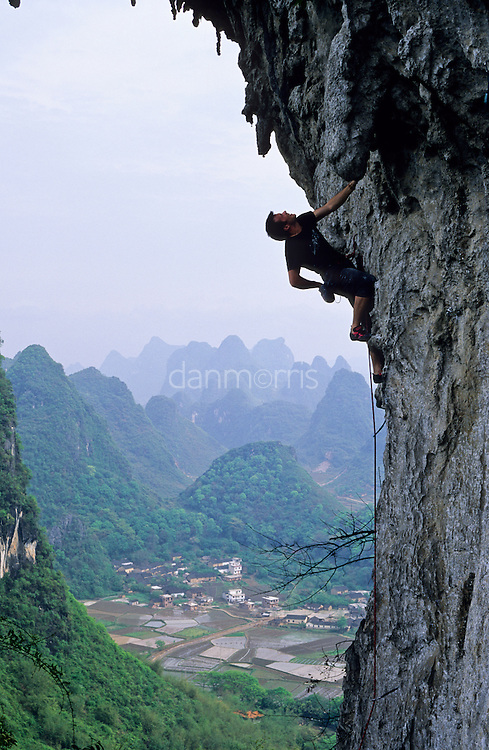 Colin Spark climbs the unusual overhanging limestone arch of Moon Hill against a backdrop of karst towers and rice paddies, Yangshuo, Guilin, China