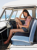 Young Woman sitting in van full length