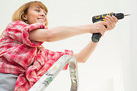 Woman drilling wall in new house