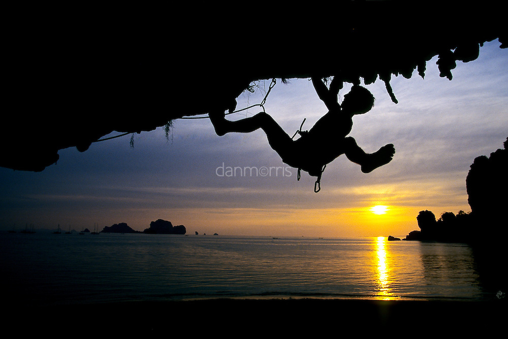 Silhouetted Frenchman Arnaud Petit climbing barefoot at sunset on Tidal Wave, 7b+, Tonsai Beach, Thailand