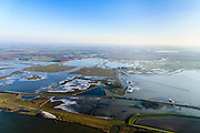Nederland, Zuid-Holland, Biesbos, 07-02-2018; Polder de Noordwaard in de Biesbosch. In het kader van Ruimte voor de Rivier' (bescherming tegen hoogwater door rivierverruiming) is de dijk van de Merwede gedeeltelijke afgraven en zijn de doorstroomopeningen / inlaten  voorzien van bruggen. Winterse opname met ijs.<br /> Doel is het maken van een doorstroomgebied (naar rechtsboven), bij hoge waterstanden zal het water van de Nieuwe Merwede afgeleid worden en zo westelijk naar het Hollandsch Diep afgevoerd worden. De kans op overstromingen (in de bovenloop) is hierdoor kleiner. Landart from artist Paul de Kort, Growing Moon: depending on the height of the tide, the spiral willl be more or less visible. The art work lies in Polder Noordwaard (part of Biesbosch National Park), part of the program 'Room for the River' (protection against high water by means of creating space for rivers). The former polder can store water and allows the river to flood more easily downstream. These measures dimishes the risk of floods further upstream at high water in the winter.<br /> luchtfoto (toeslag op standard tarieven);<br /> aerial photo (additional fee required);<br /> copyright foto/photo Siebe Swart