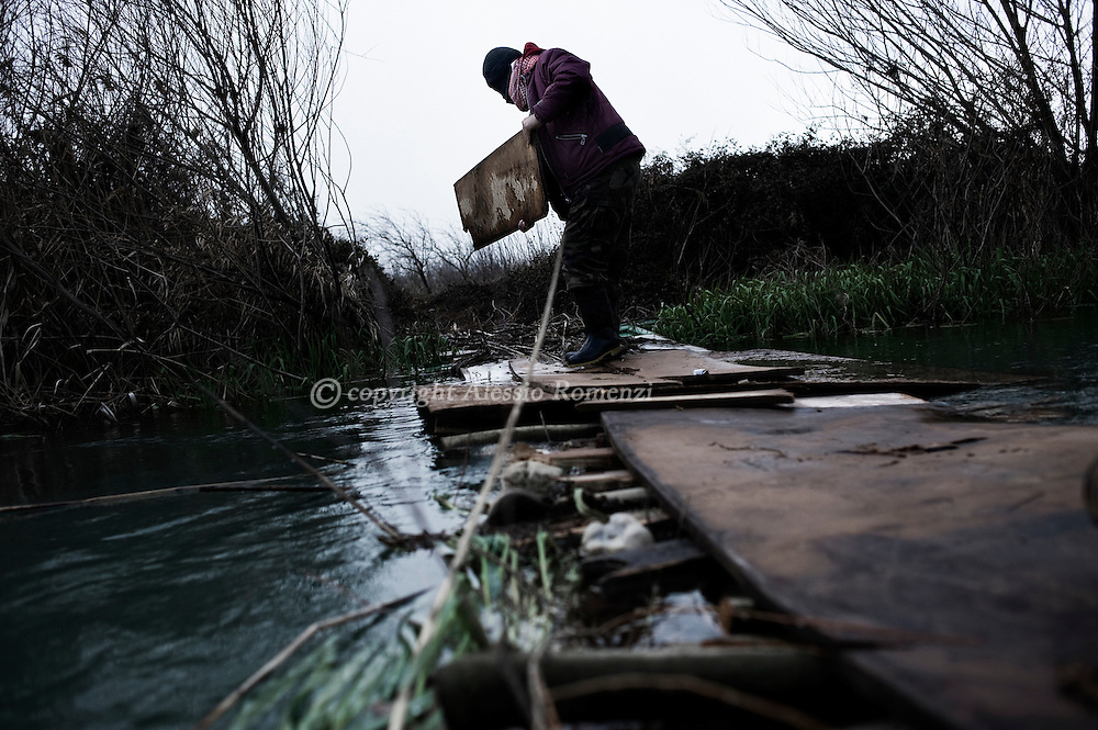 SYRIA - Homs province: This picture shows a Free Syrian Army soldier as he is building a bridge on a river to evacuate wounded in the countryside of Homs on February 18, 2012. ALESSIO ROMENZI