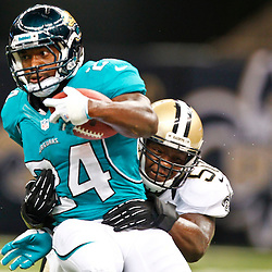 August 17, 2012; New Orleans, LA, USA; Jacksonville Jaguars running back Montell Owens (24) is tackled by New Orleans Saints linebacker Curtis Lofton (50) during the first half of a preseason game at the Mercedes-Benz Superdome. Mandatory Credit: Derick E. Hingle-US PRESSWIRE