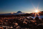 tussock, snow and rock dominate this mountain sunrise at mt ruapehu, with mount doom rising above the mountain cloud in the background, tongariro national park, new zealand