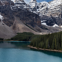 A couple canoes across Moraine Lake in Banff National Park on a picturesque fall day.