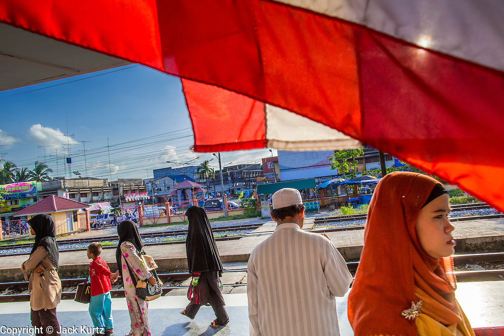 27 OCTOBER 2012 - SUNGAI KOLOK, NARATHIWAT, THAILAND:     Thai Muslims walk past a Thai flag hanging in a train station north of Sungai Kolok, Thailand. Sungai Kolok has been a center of extremist violence. Several car bombs have been detonated in the city, which is on the Malaysian border and very popular with Malaysian tourists. More than 5,000 people have been killed and over 9,000 hurt in more than 11,000 incidents, or about 3.5 a day, in Thailand's three southernmost provinces and four districts of Songkhla since the insurgent violence erupted in January 2004, according to Deep South Watch, an independent research organization that monitors violence in Thailand's deep south region that borders Malaysia.   PHOTO BY JACK KURTZ