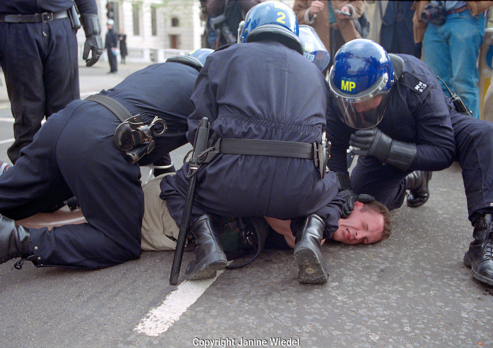 Protester being arrested by police at May Day demonstration  reclaim the streets in Trafalgar Square in central London 2000.