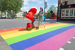 ©Licensed to London News Pictures 16/06/2020<br /> Woolwich, UK. A mum pushing a red pushchair across a colourful crossing in Woolwich town centre, Woolwich. Rainbow pedestrian crossings return to Greenwich Borough to show support for Gay pride month. Crossings in Eltham,Greenwich, plumstead,Charlton and Woolwich have had a rainbow make over bringing some colour to the streets in South East London. Photo credit: Grant Falvey/LNP