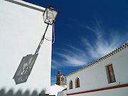 The Church of San Pedro and a typical street scene in the white-washed village of Arcos de la Frontera, Andalusia, Spain.
