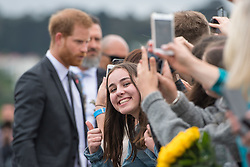 A woman leans out to have her photo taken with the Duke of Sussex during a public walkabout on a visit to the newly unveiled UK war memorial and Pukeahu National War Memorial Park, in Wellington, on day one of the royal couple's tour of New Zealand.