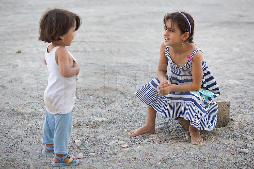 © Licensed to London News Pictures. 27/07/2014. Hamdaniyah, Iraq. Dilar Minowar Salim, 9, an Iraqi Christian refugee from Mosul, talks to her sister, Rania, 5, on the road outside the partially built house they inhabit with 15 members of their extended family in Hamdaniyah, Iraq.<br /> <br /> Having taken over Mosul Iraq's second largest city in June 2014, fighter of the Islamic State (formerly known as ISIS) have systematically expelled the cities Christian population. Despite having been present in the city for more than 1600 years, Christians in the city were given just days to either convert to Islam, pay a tax for being Christian or leave; many of those that left were also robbed at gunpoint as they passed through ISIS checkpoints. Photo credit: Matt Cetti-Roberts/LNP