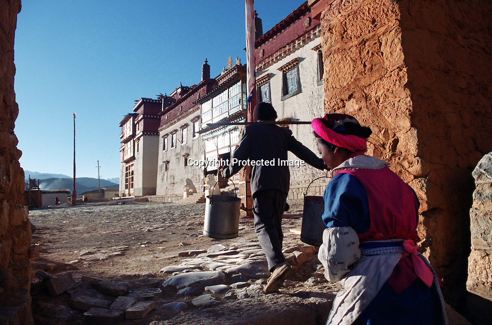 "ZHONGDIAN COUNTY, DECEMBER 19, 2000: Tibetans walk through the gate of Songzanlin monastery, Yunnan province , December 19, 2000..Zhongdian county is believed to be part of the areas on which James Hilton's famous novel "" lost Horizon""- a description of Shangri-La- is modelled.. ."