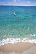 Aerial view of fishing boat anchor off of beach in clear calm water.  Waves lapping onto beach