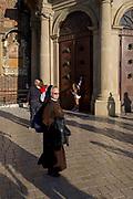 A nun walks past tourists outside the Church of St Mary on Rynek Glowny market square, on 22nd September 2019, in Krakow, Malopolska, Poland.