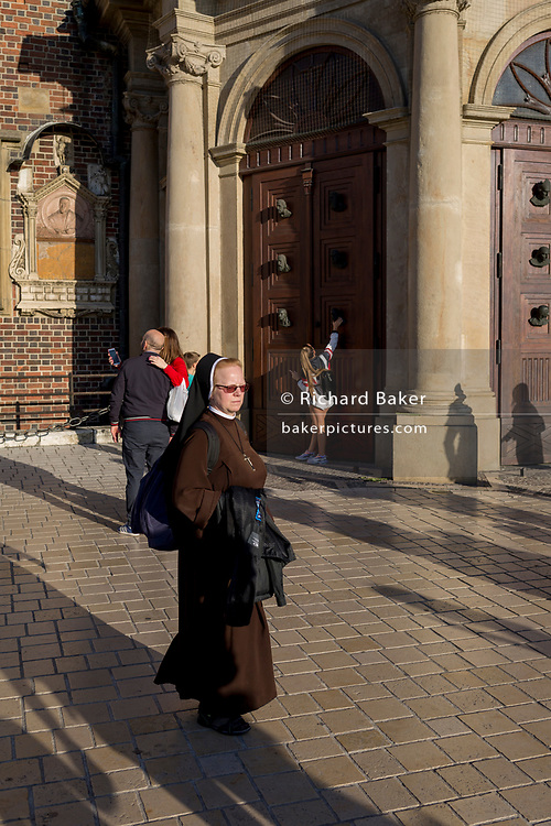 A nun walks past tourists outside the Church of St Mary on Rynek Glowny market square, on 22nd September 2019, in Krakow, Malopolska, Poland.