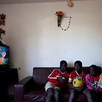 "The Aguek children, Sudanese refugees, watch a cartoon on the sudanese chanel in their living room in the SinSin building on February 28 2011 in Eilat. The municipality hung 1,500 red flags around the city as a sign of warning and put up hundreds of banners reading: ""Protecting our home, the residents of Eilat are drawing the line on infiltration."" Eilat Mayor Meir Yitzhak Halevi said that 10 percent of the city's population was currently made up of migrants and that the residents feel that the city has been conquered...Photo by Olivier Fitoussi."