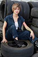 Portrait of a young mechanic sitting on tires in car workshop