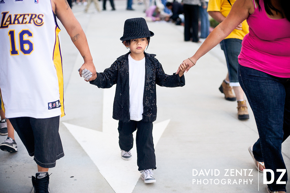 Dressed in vintage Michael Jackson attire, Victor Chupina, 5, of East Los Angeles, walks with his parents while joining hundreds of other fans and members of the media outside the UCLA Medical Center in Los Angeles, Calif., to mourn the death and pay tribute to the life of Michael Jackson, who died earlier that day at the age of 50, on Thursday, June 25, 2009.