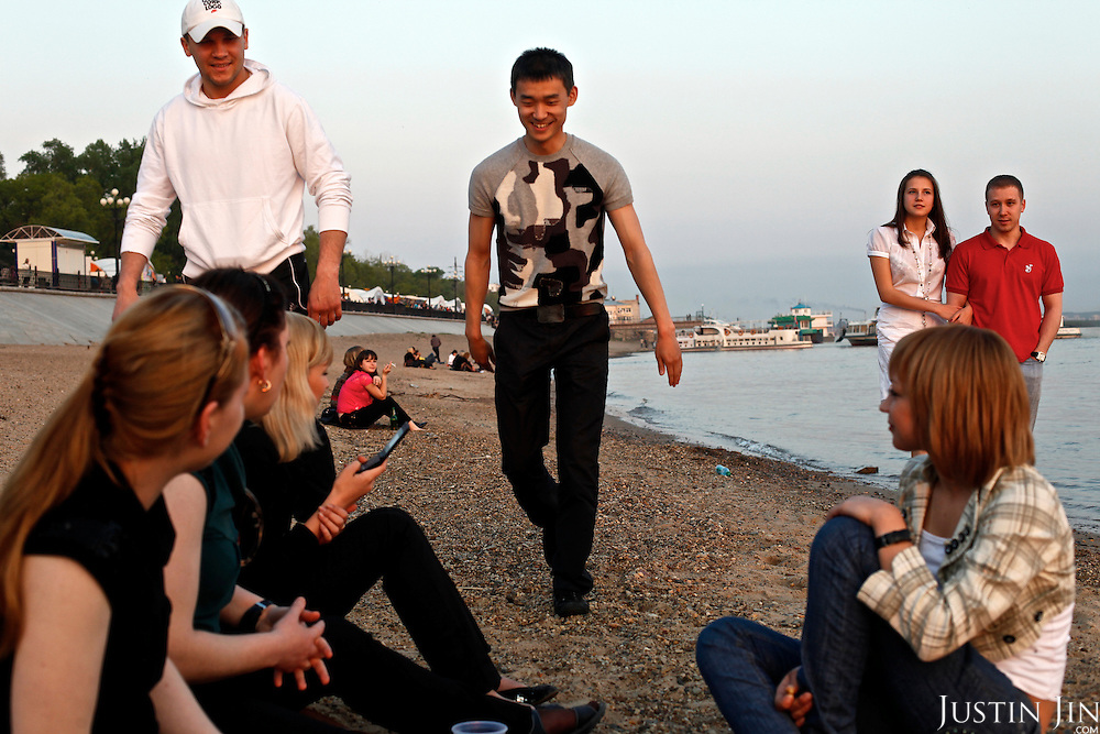 Chinese youngster Qi (surname) Ke hangs out with Russian friends on the bank of Amur River in Khabarovsk city in Russia. Amur is part of the border that separates China from Russia.