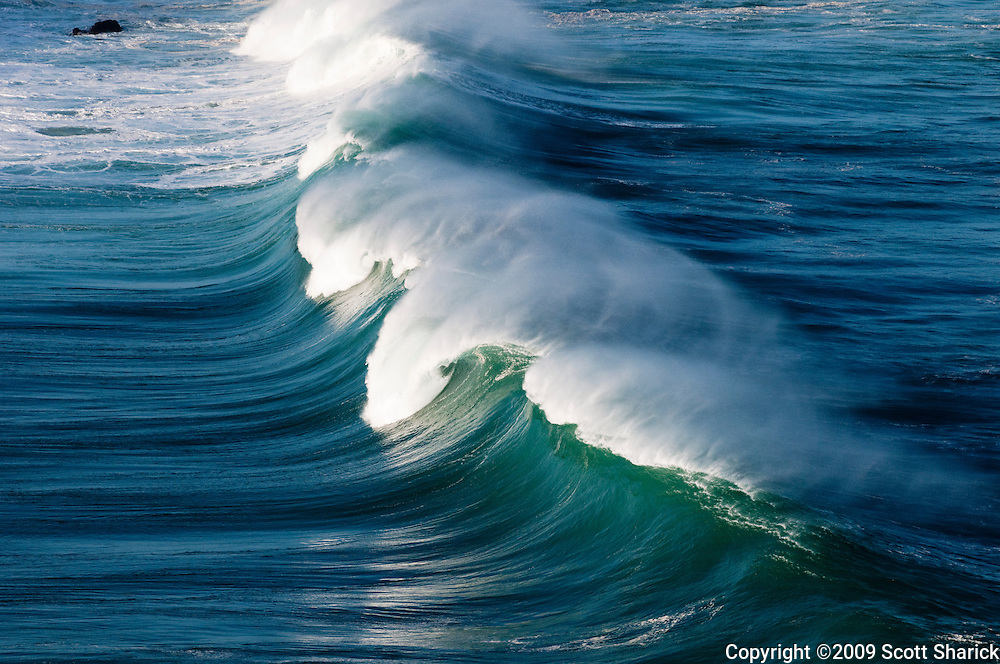 The early morning sun lights up a wave at Waimea Bay on Oahu, Hawaii.