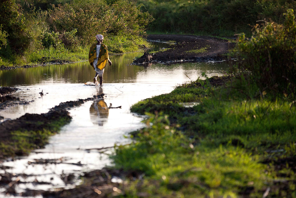 An elderly women wades through a flooded road in Kenya as it is the most viable route for reaching her home.