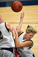 Timberlake High's Caitlyn Nichols crashes into her teammate and a Fruitland High defender during a game Thursday in the 3A girls state basketball tournament at Skyview High School in Nampa.