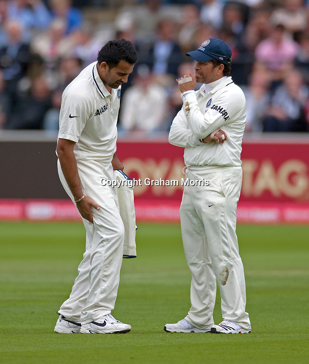 Bowler Zaheer Khan limps off into the pavilion holding his hamstring past Sachin Tendulkar (right) during the first npower Test Match between England and India at Lord's Cricket Ground, London.  Photo: Graham Morris (Tel: +44(0)20 8969 4192 Email: sales@cricketpix.com) 21/07/11