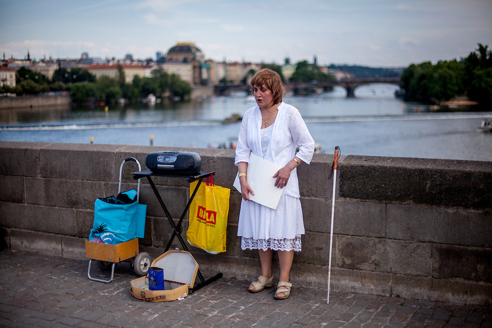 A blind woman sings at Charles Bridge during a Saturday afternoon. Every artist working on Charles Bridge has to go through a selection process in front of a jury to get permission to work on the bridge.