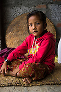 Monika (7) poses for a portrait in her temporary home in Chautara, Sindhupalchowk, Nepal on 29 June 2015. Monika (7), Aastha (6) and Sapana Baniya (2 months) lost their mother during the April 25th earthquake that completely levelled their house. Aastha was buried under the rubble together with her mother but Aastha survived. As their father Ratna Baniya (28) cannot care for the children on his own, SOS Childrens Villages has since been supporting their grandmother Bhagawati Baniya (56) with financial and social support so that she can manage to raise the children comfortably and ensure that they will all be schooled. Photo by Suzanne Lee for SOS Children's Villages