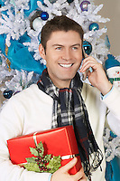 Man using cell phone holding present in front of Christmas tree