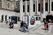 City workers enjoy spring sunshine during their lunch hours at the Guildhall, next to an outdoor photography exhibition on the theme of mental health, in the City of London, the capital's ancient, financial district, on 14th May, in London, England. Located in the courtyard of Guildhall Yard, Let's Talk is a collaboration between photographer Charlie Clift and artist Kate Forrester. It takes the form of a series of large photographs of celebrities