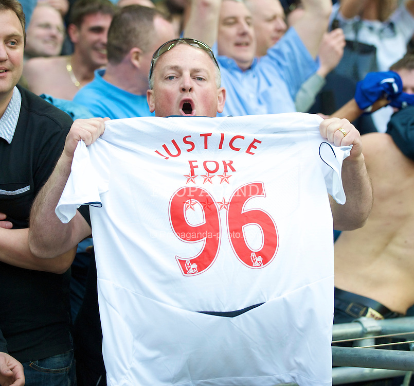 """LONDON, ENGLAND - Sunday, April 19, 2009: An Everton supporter holds up a shirt with """"Justice for 96""""  on it in support of the 96 Liverpool supporters who lost their lives in the Hillsborough Stadium Disaster at an FA Cup semi-final 20 years ago; after his side's penalty shoot-out victory over Manchester United the FA Cup Semi-Final match at Wembley. (Photo by David Rawcliffe/Propaganda)"""
