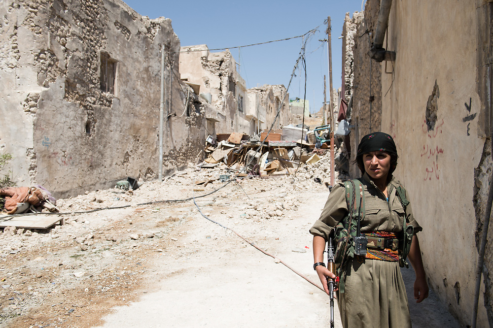 A female fighter of People's Defence Forces walking in a street in Shingal (Sinjar), Iraq, August 27, 2015