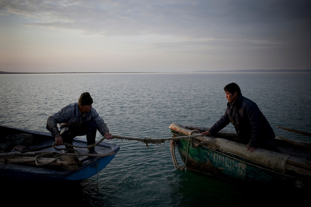 CREDIT: DOMINIC BRACCO II..SLUG:PRJ/KAZAKHSTAN..DATE:11/1/2009..CAPTION:From left, Rustem Baizhanov, 30 of Aralsk, pulls in Gaziz Yelusizov 23 of Aralsk, to board his boat while fishing on the Aral Sea on November 1, 2009...Aral Sea Overview: ..During the 1960s the USSR began irrigating the waters of the Aral Sea in southern Kazakhstan to combat their growing food crisis. The Soviets severely miscalculated and water began receding quickly from the port cities. The waters continued to recede. By 2000 the water was 80 km away from the city of Aralsk, a main seaport in Kazakhstan. In 2005 with help from the World Bank, construction began on a 13km dike that locals hoped would bring the waters back to their original shores. The project raised water quality and fishing was able to resume, however four years after completion of the dike the water is still 50km from Aralsk's port. Locals seem mixed on the possibility of the sea returning after more than 40 years without the sea. Fishermen from Aralsk make a three-hour path through soft desert road along the former seabed. The only source of income for many is cattle, horses, and camels, which have, began to overgraze the areas of the former seabed and surrounding desert. Because of this nutrient rich topsoil is lifted by the wind and the process of desertification continues.  .