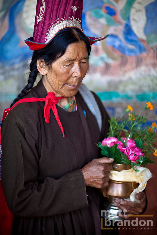 A Ladakhi woman in traditional clothing brings an offering to the monks.