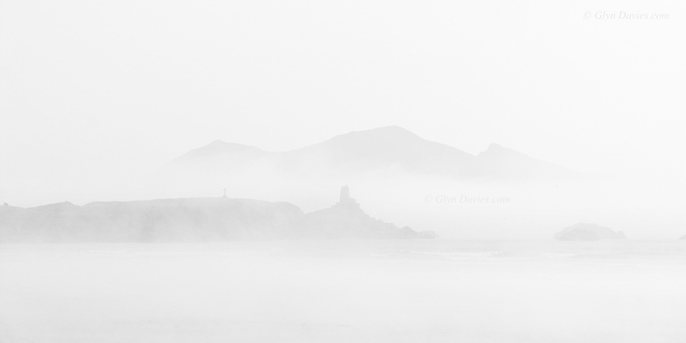 Llanddwyn Island and Malltraeth Beach, shrouded in thick sea fog on the West coast of Anglesey. Beyond, across Caernarfon Bay, on the Welsh mainland, can be seen the three peaks of Yr Eifl, from L-R Tre'r Ceiri the iron age hill fort, Garn Ganol and Garn For on the Llyn Peninsula.