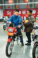 Men shopping for new motorcycle in Chinese manufacturer Qingqi motorbike sales showroom in Jinan city, Shandong Province, China