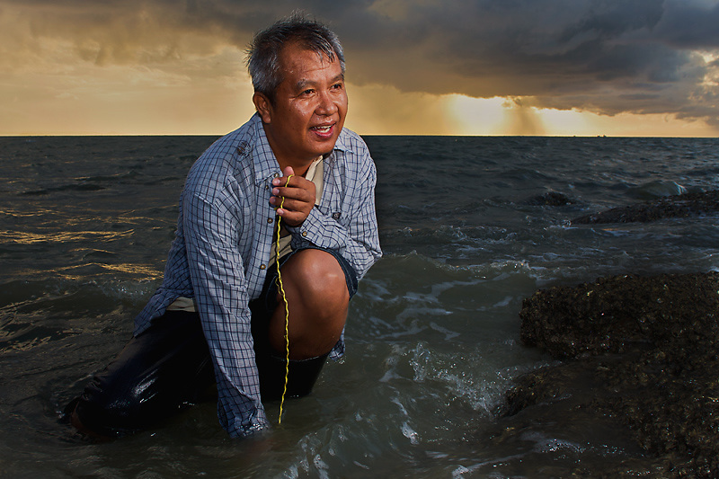 A Man, fishing for dinner at a beach of Pattaya during sunset