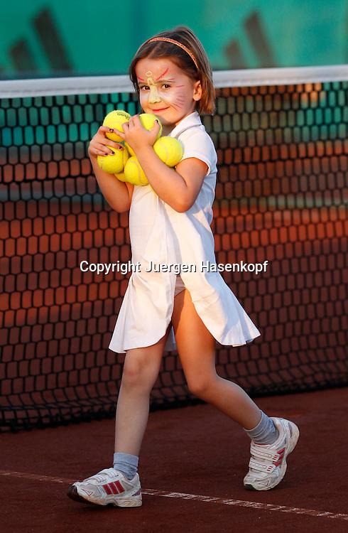 Ali Bey Manavgat Tennis Camp,Tuerkei, kleines Maedchen (4) mit Gesichtsbemalung ?sammelt Tennisbaelle auf, traegt viele Baelle auf dem Arm,.Ganzkoerper,Hochformat,