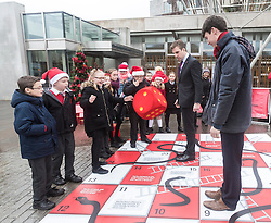 """Campaigners from Shelter Scotland raise awareness of their campaign """"Homelessness - Far From Fixed"""" outside the Scottish Parliament in Edinburgh. They are joined by carol singers from Corstorphine Primary School, a Christmas tree and a giant snakes and ladders board game - Chance Not Choice - which illustrates how life chances affect people's ability to keep a roof over their head.<br /> <br /> Pictured: Daniel Johnson from Scottish Labour playing Chance Not Choice with Evan Jones from Costorphine Primary School throwing the dice"""