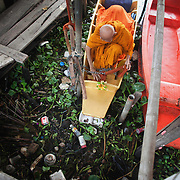 Thai Buddhist monk Luang Pho Malai, 91 years old, unties his boat Saturday, June 29, 2013, prior to making his morning round on the outskirts of Bangkok.   For the past 30 years Luang Pho Malai has made his daily round to attend to the faithful in a small wooden boat to collect their offers and dispense blessings.  While many of Bangkok's major canals were filled in and paved over during the building boom of the 1980's klong Thavi Watthana still serves the needs of a impoverished community.